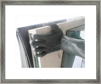 an arm holding a building in Lisbon Framed Print