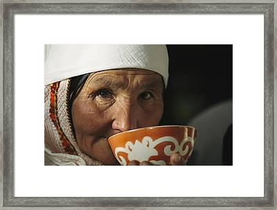 An Elderly Woman Drinks From A Cup Framed Print by David Edwards