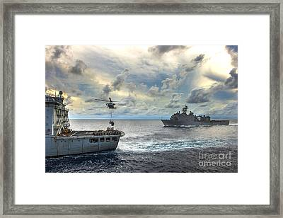 An Mh-60s Sea Hawk Helicopter  Lifts Pallets Of Supplies Framed Print