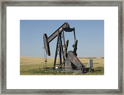 An Oil Rig Pumps Oil From The Montana Framed Print by Joel Sartore