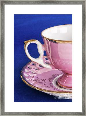 Antique Pink Cup And Saucer On Blue Textured Background Framed Print by Vizual Studio