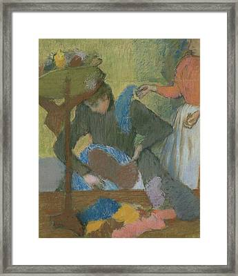 At The Hat Maker Framed Print by Edgar Degas
