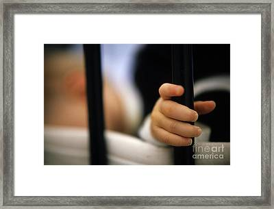Baby Girl Holding Bar Of Cot Framed Print by Sami Sarkis