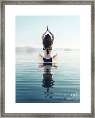 Back Of A Woman Practicing Yoga Meditation On The Water In Sunri Framed Print
