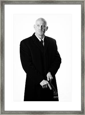 Bald Headed Man Wearing Heavy Black Overcoat Cocking Automatic Pistol Framed Print by Joe Fox