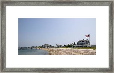 Beach With Buildings In The Background Framed Print