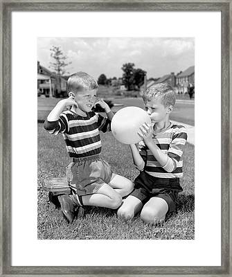 Boy Blowing Balloon While Another Framed Print by H. Armstrong Roberts/ClassicStock