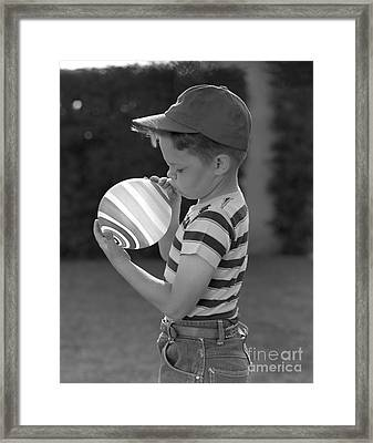 Boy Blowing Up A Striped Balloon Framed Print by Pound/ClassicStock
