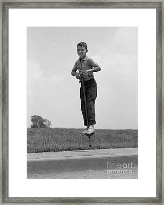 Boy Jumping On Pogo Stick, C.1960s Framed Print by H. Armstrong Roberts/ClassicStock