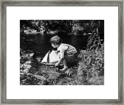 Boy Putting Toy Sailboat Into Stream Framed Print