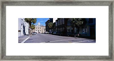 Buildings On Both Sides Of A Road Framed Print