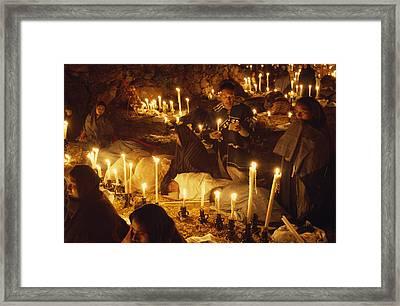 Candles Light A Cemetery Where Indians Framed Print by W.E. Garrett
