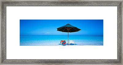 Chairs Under An Umbrella On The Beach Framed Print
