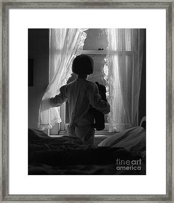 Child Looking Out Window At Night Framed Print by H. Armstrong Roberts/ClassicStock