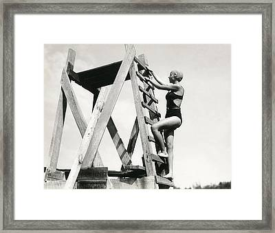 Climbing Up The High Dive Framed Print by Underwood Archives