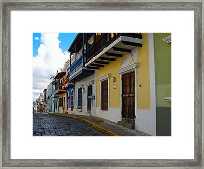 Colorful Houses Along A Cobblestone Street Framed Print by George Oze