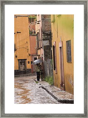 Couple Walking In The Rain Through Old San Miguel Mexico Framed Print by Juli Scalzi