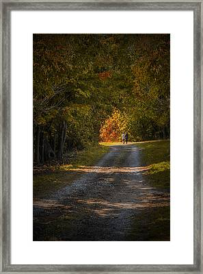 Couple Walking On A Dirt Road Through A Tree Canopy During Autumn Framed Print