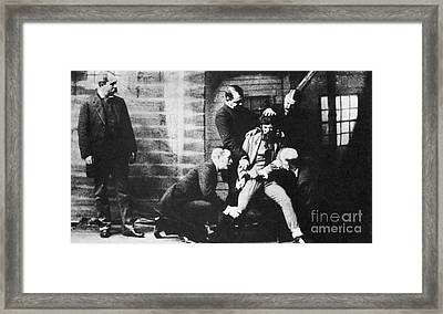 Criminal Being Held Down For Mug Shot Framed Print by Photo Researchers