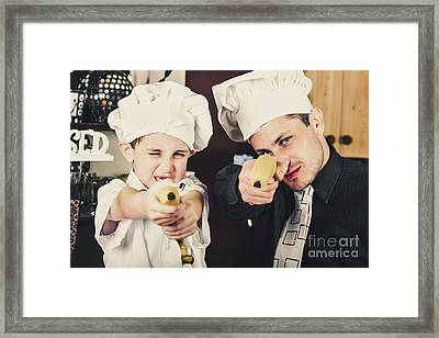 Dad And Son Cooks Shooting With Bananas In Kitchen Framed Print