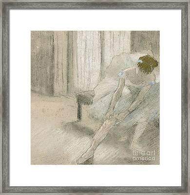 Dancer Seated, Readjusting Her Stocking Framed Print by Edgar Degas