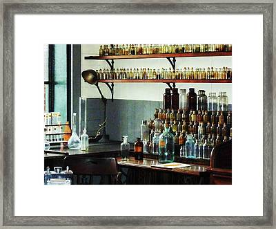 Desk With Bottles Of Chemicals Framed Print by Susan Savad