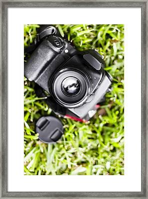 Digital Slr Camera On Green Grassy Field Framed Print by Jorgo Photography - Wall Art Gallery