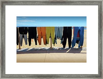 Drying Wet Suits Framed Print by Carlos Caetano