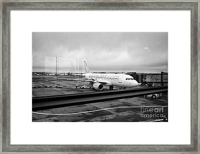 easyjet aircraft on stand at departures gate Keflavik airport looking through the window glass Icela Framed Print by Joe Fox