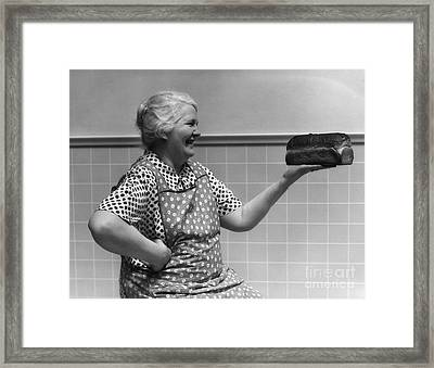 Elderly Woman Admiring Loaf Of Bread Framed Print by H. Armstrong Roberts/ClassicStock