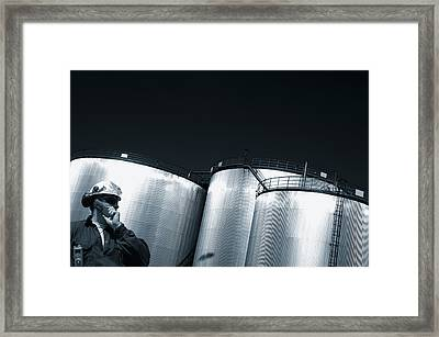 Engineer And Oil Towers At Sunset Framed Print by Christian Lagereek