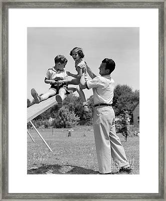 Father Lifting Kids Onto Seesaw, C.1950s Framed Print by H. Armstrong Roberts/ClassicStock