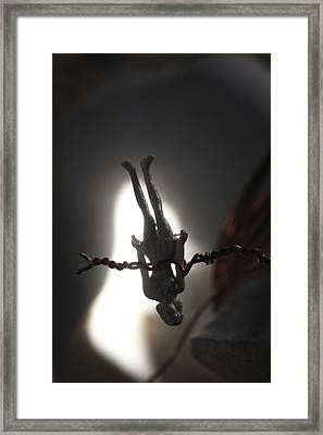 Figurine Of A Woman Hanging Upside Down Framed Print