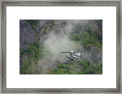 Float Plane Against Granite Cliff Framed Print by Ralph Lee Hopkins