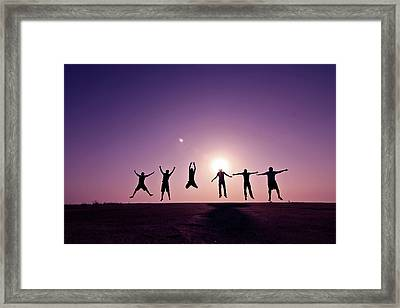 Friends Jumping Against Sunset Framed Print