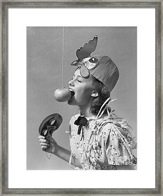 Girl Bobbing For Apple On String Framed Print by H. Armstrong Roberts/ClassicStock
