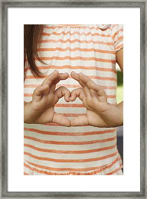 Girl Making Heart Shape With Fingers Framed Print by Gillham Studios