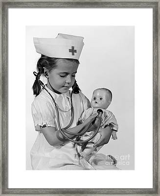 Girl Playing Nurse With Doll, C.1960s Framed Print