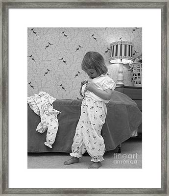 Girl Putting On Pajamas, C.1960s Framed Print