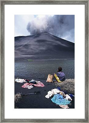 Girl Washing Clothes In A Lake With The Mount Yasur Volcano Emitting Smoke In The Background Framed Print by Sami Sarkis