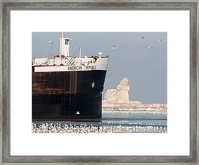 Great Lakes Ship Passing A Frozen Cleveland Lighthouse Framed Print