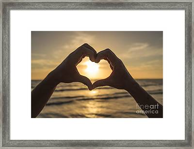 Hands Forming Heart Around Sunset Framed Print by Edward Fielding