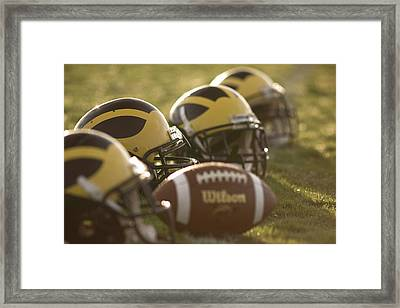 Helmets And A Football On The Field At Dawn Framed Print