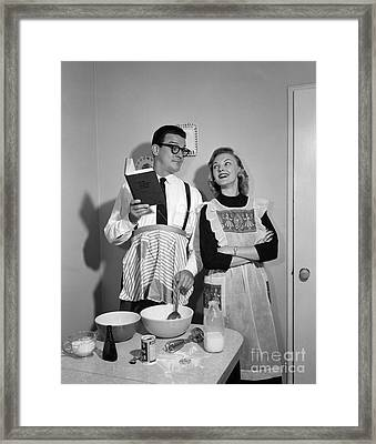 Husband Trying To Cook While Wife Looks Framed Print