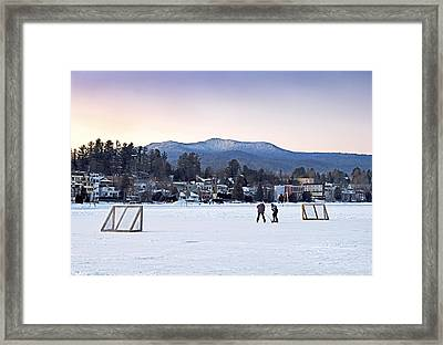 Kids Playing Hockey On Mirror Lake With Lake Placid Village Shown In The Background At Sunset  Framed Print by Brendan Reals