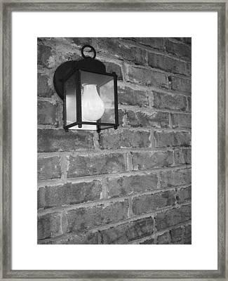 Lantern On Brick Wall  Framed Print by Nicole Aponte