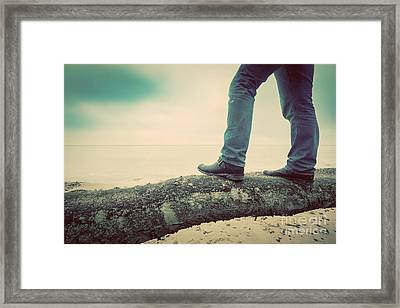 Man In Jeans And Elegant Shoes Standing On Fallen Tree On Wild Beach Looking At Sea. Vintage Framed Print