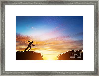 Man Running Fast To Jump Over Precipice Between Two Mountains Framed Print