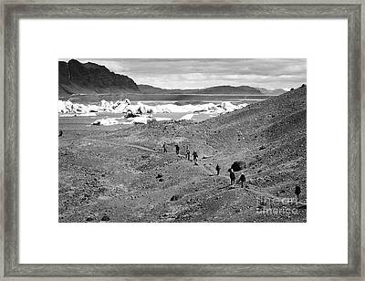middle aged tourists walking designated pathway at Jokulsarlon glacial lagoon Iceland Framed Print