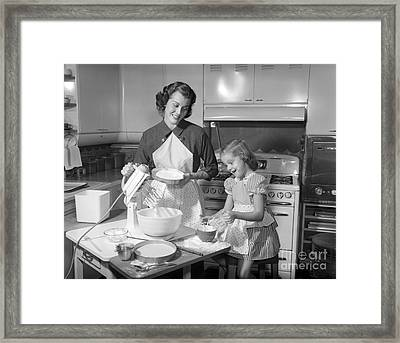 Mother And Daughter Baking A Cake Framed Print